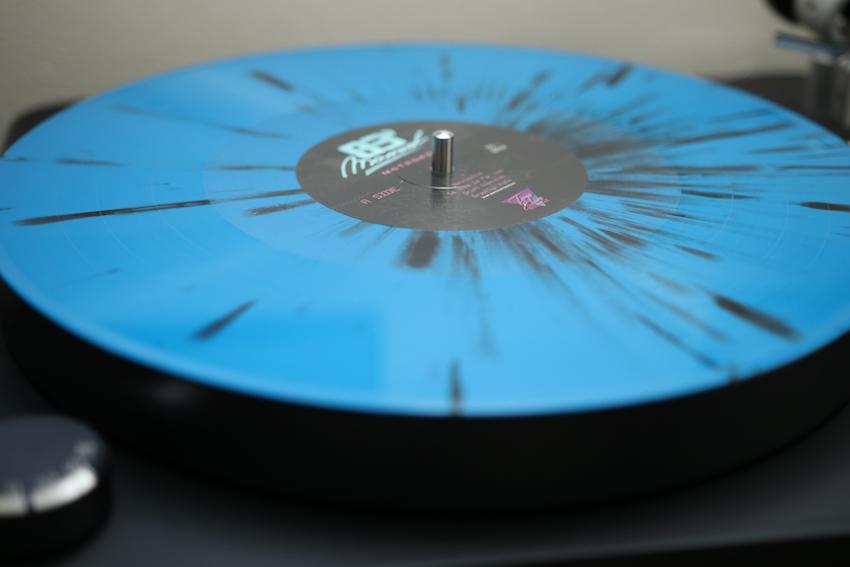 The vinyl record for Marvel83's Metropolis comes on blue vinyl with black splatter.